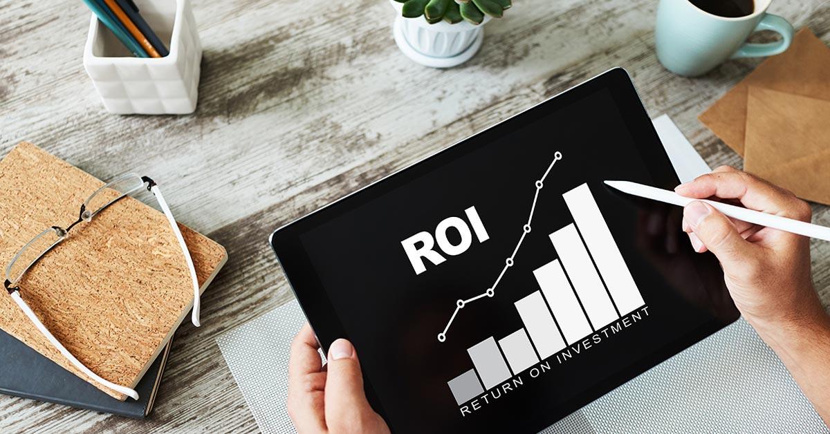 """Eine Person hält ein Tablet in der Hand, auf dem ein Diagramm und """"ROI - Return on Investment"""" steht."""