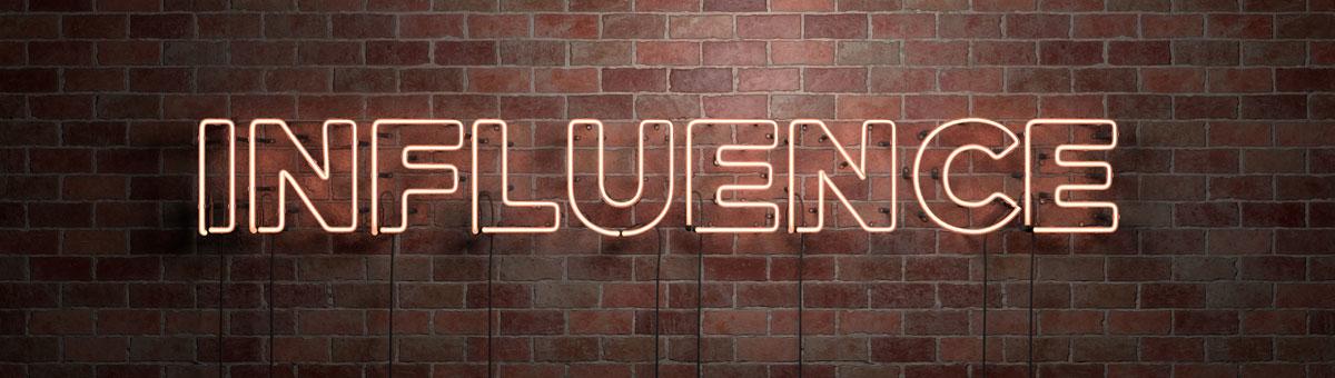 """An einer Steinmauer wurde der Schriftzug """"Influence"""" in Neonröhren angebracht."""