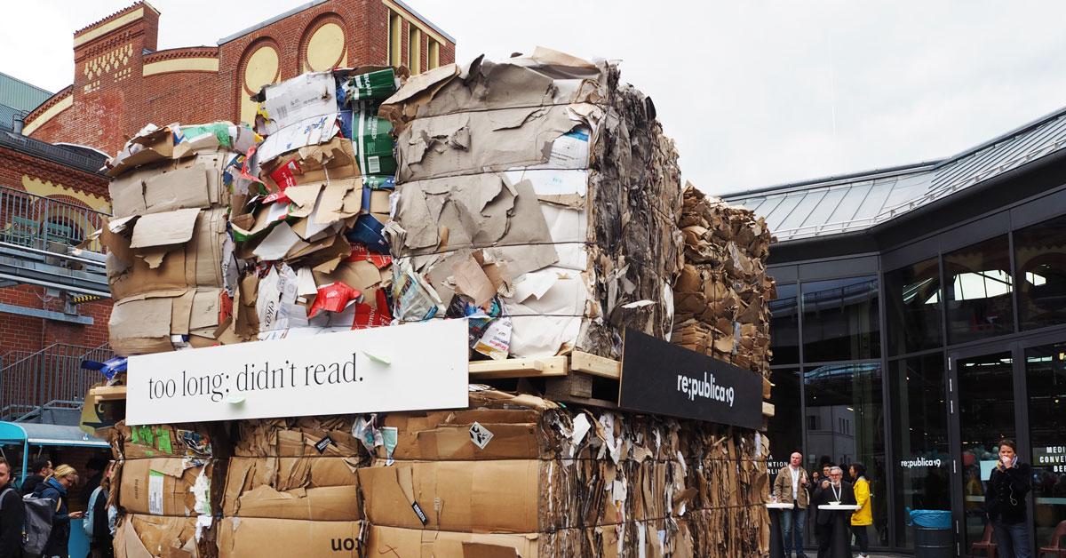 Auf dem Bild sieht man Kartons voll ungelesener Reklamezeitschriften. Davor das Motto der re:publica 2019: Too long; didn't read.