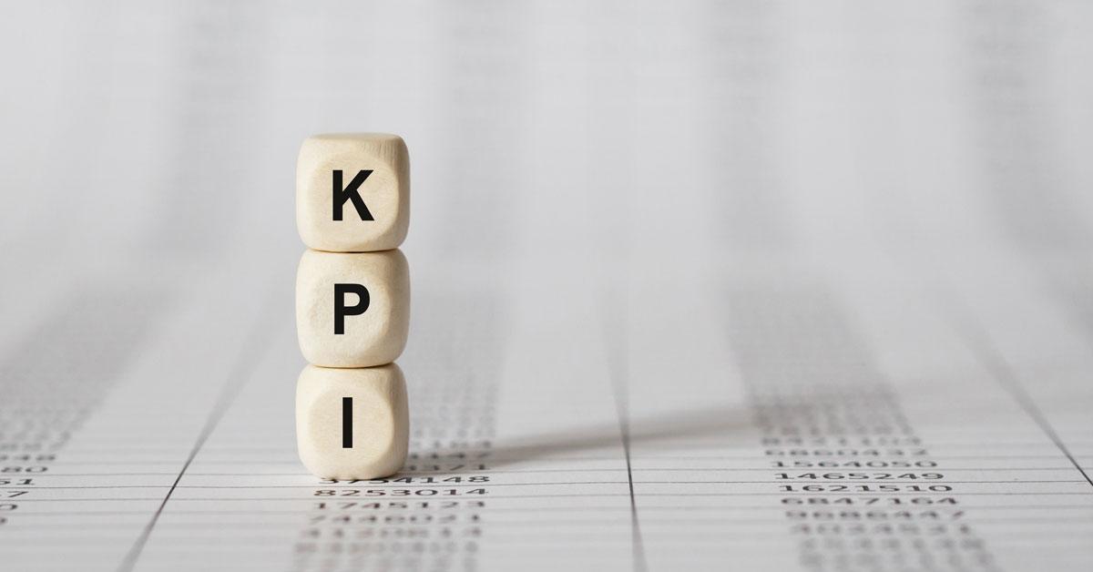 Auf dem Bild sieht man Würfel mit der Aufschrift KPI, die auf einer ausgedruckten Excel-Liste liegen.
