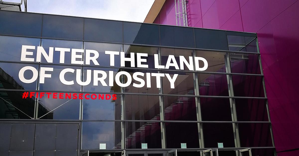 """Auf dem Bild sieht man den Eingang zum Fifteen Seconds Festival. Auf der Glasfront steht """"Enter the land of curiosity."""""""