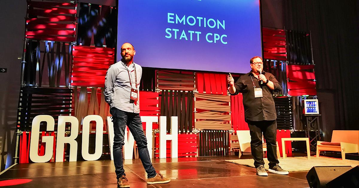 """Zwei Vortragende stehen auf einer Bühne, auf der Leinwand hinter ihnen steht: """"Emotion statt CPC""""."""