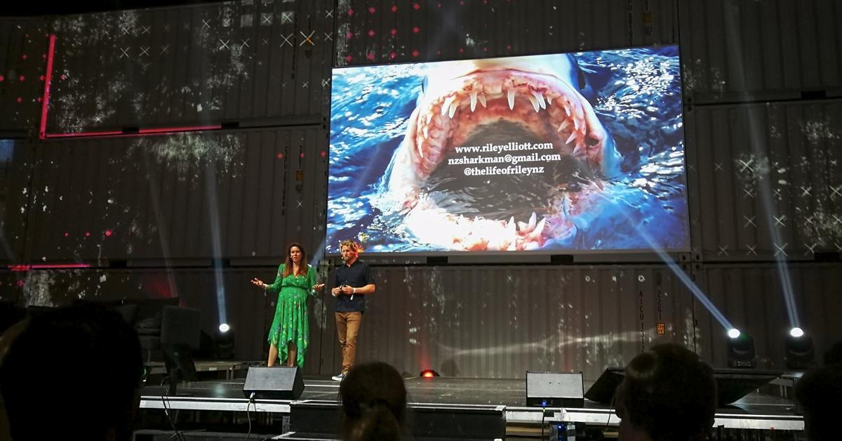 Zwei Vortragende stehen auf einer Bühne, auf der Leinwand hinter ihnen sieht man ein geöffnetes Haifischmaul, das aus dem Wasser ragt.