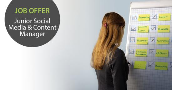 """Links im Bild der Text """"Job-Offer: Junior Social Media & Content Manager"""", rechts im Bild schreibt eine Frau etwas auf eine Flipchart."""