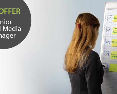 """Links im Bild der Text """"Job-Offer: Senior Social Media Manager"""", rechts im Bild schreibt eine Frau etwas auf eine Flipchart."""