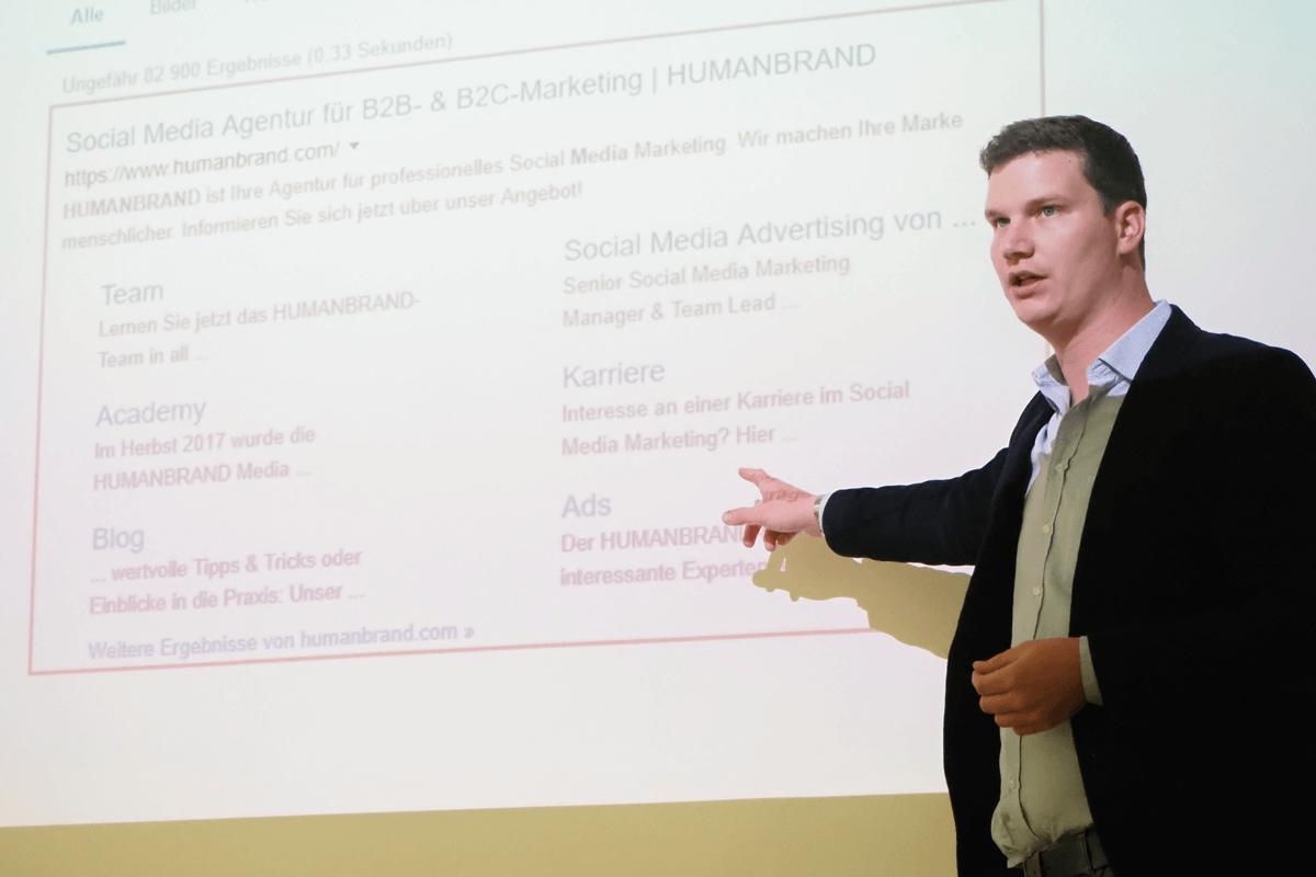 Ein Mann steht vor einer Leinwand, auf der das Google-Suchergebnis der HUMANBRAND Media GmbH zu sehen ist.