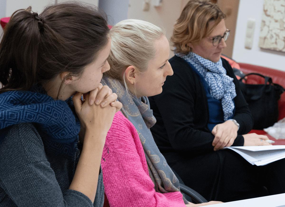 Drei Frauen sitzen nebeneinander und hören dem Vortragenden zu.