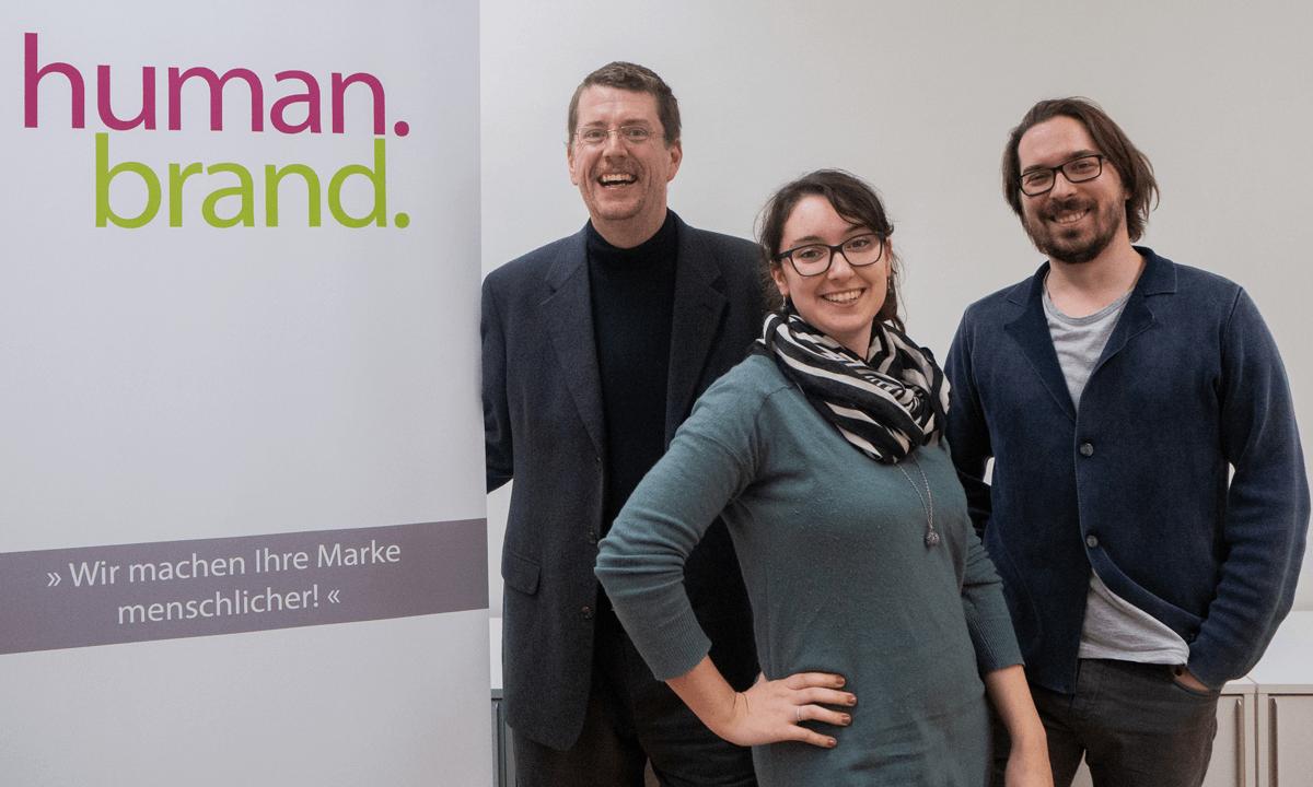 Die beiden Referenten Christian Haberl und Gabriel Schwarzinger und die Referentin Petra Herold stehen neben einem Roll-up, auf dem HUMANBRAND geschrieben steht.