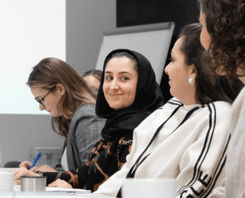 Das Bild zeigt vier Frauen, die in einer Reihe sitzen. Manche sehen auf die Leinwand im Hintergrund, andere notieren Informationen. Eine von ihnen lächelt in die Kamera.