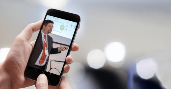 Eine Hand hält ein Smartphone, auf dessen Bildschirm ein Vortragender auf einer Messe zu sehen ist.