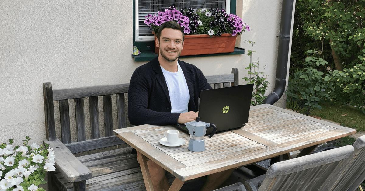 Ein dunkelhaariger junger Mann arbeitet am Laptop und lächelt in die Kamera.