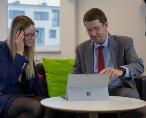 Eine blonde Frau und ein Mann schauen lächelnd auf einen Surface Bildschirm.
