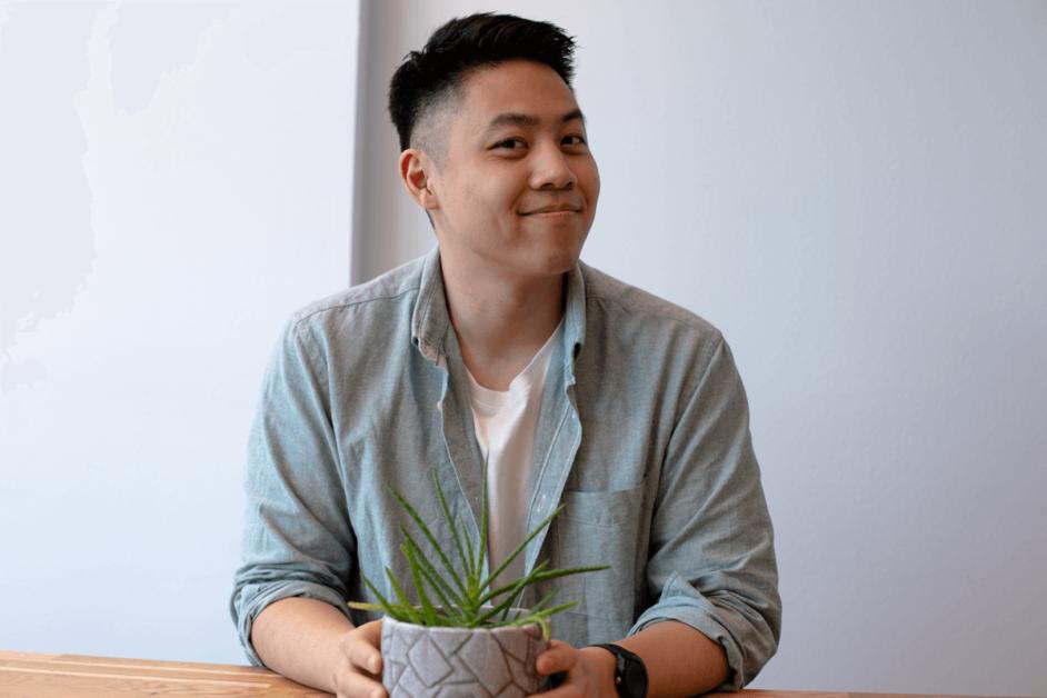 Ein junger Mann hält einen Blumentopf mit einem Kaktus in den Händen und lächelt in die Kamera.
