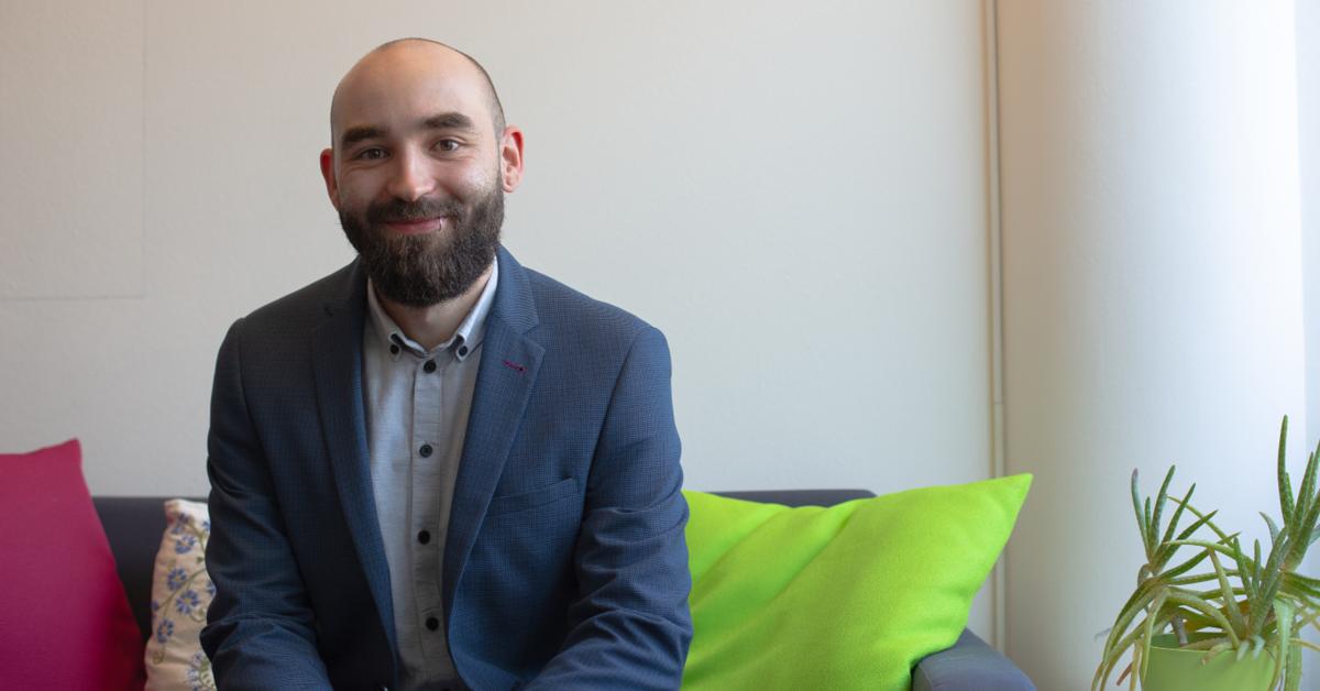 Ein Mann mit Bart im Anzug sitzt auf einer Couch und lächelt in die Kamera