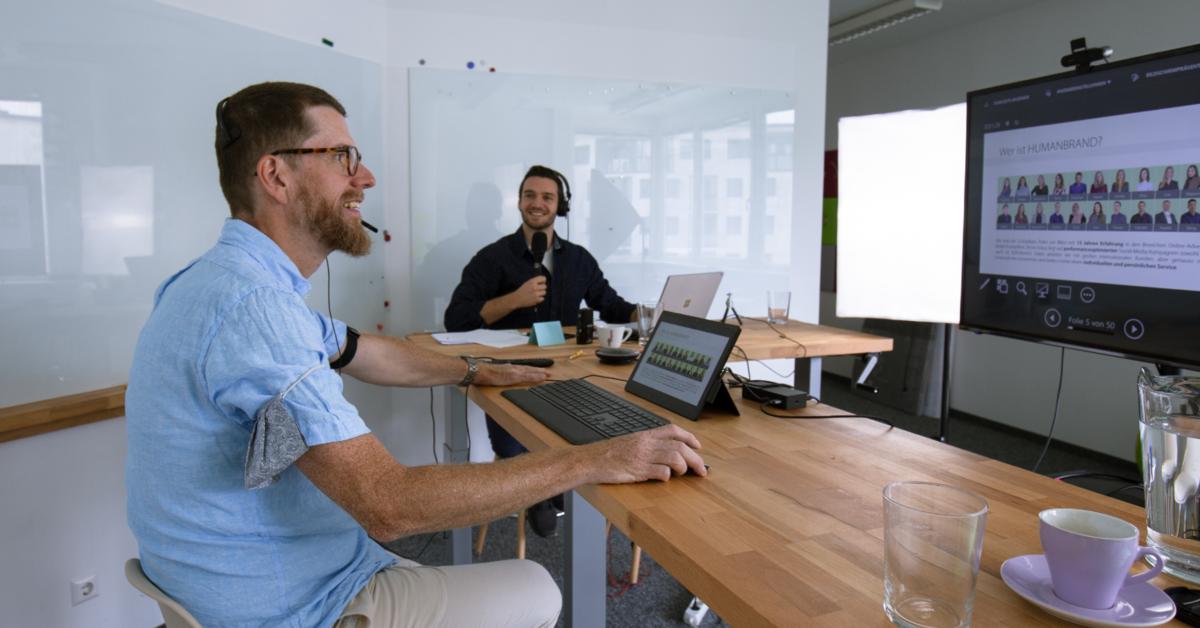 Ein Mann mit Brille und Bart sitzt an einem Tisch, schaut auf einen Laptop, im Hintergrund sieht man einen lächelnden Moderator mit Mikrofon.