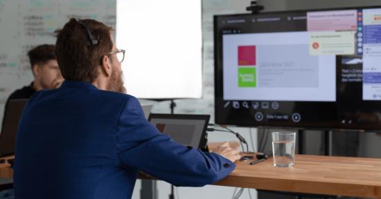 Ein Mann trägt ein Headset und sitzt vor einem Bildschirm.