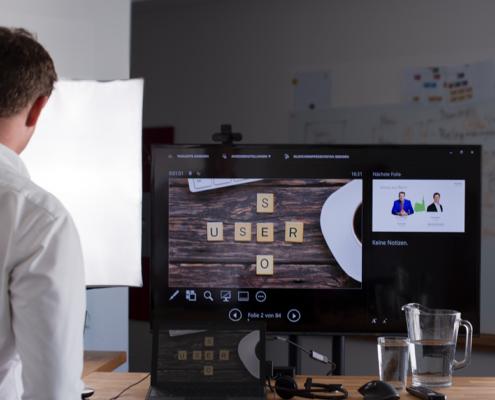 Das Bild zeigt einen Mann von hinten, der auf einen Bildschirm sieht.