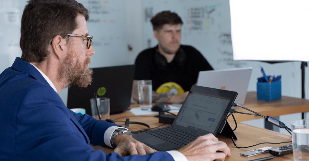 Ein Mann mit Brille sitzt an einem Tisch und arbeitet an einem Laptop.