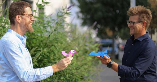 Zwei Männer stehen einander gegenüber und halten sich zwei Figuren, den Marketingvogel und die Vertriebsrakete, entgegen.