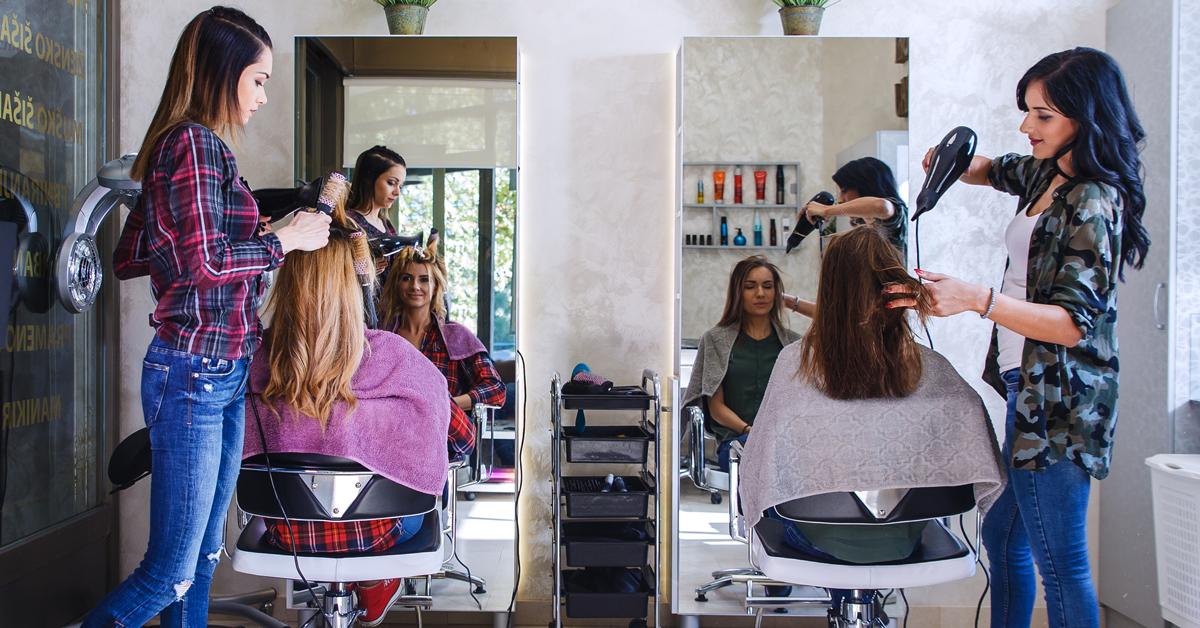 Zwei Frauen schneiden zwei Frauen im Friseurstuhl die Haare