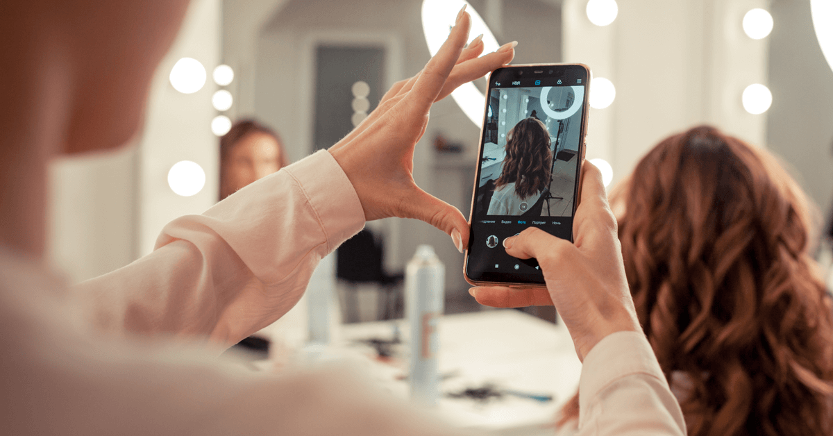 Eine Frau fotografiert die Haare einer anderen Frau beim Friseur