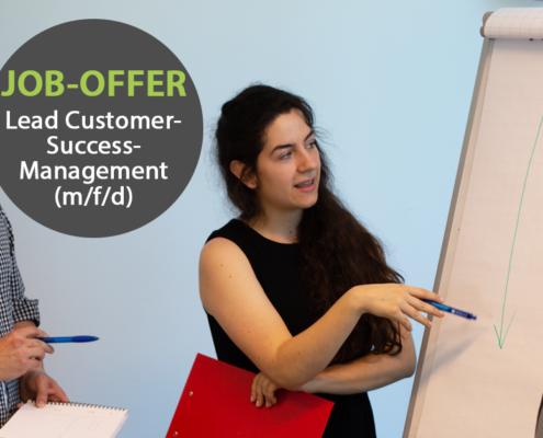 """Eine junge Frau steht neben einer Flipchart und erklärt zwei anderen Personen etwas. In einem grauen Kreis steht """"Job-Offer: Lead-Customer-Success-Management""""."""