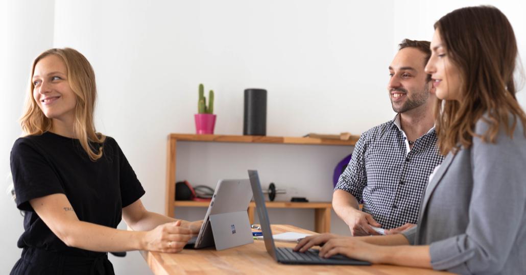 Zwei Frauen und ein Mann stehen bei einem Tisch und reden, arbeiten am Laptop