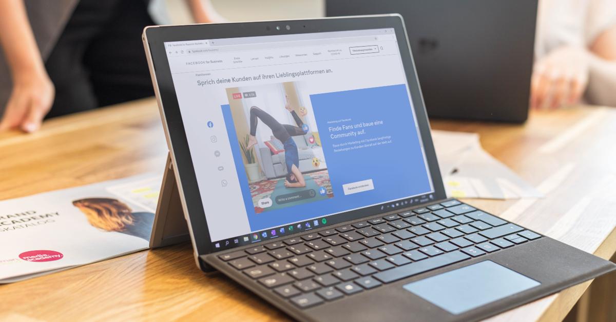 Ein Laptop steht auf einem Holztisch. Auf seinem Display ist eine Facebook-Anzeige zu sehen.