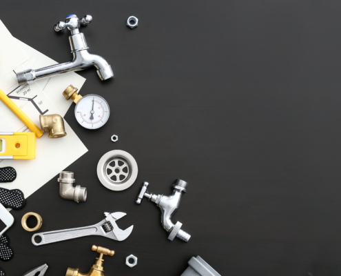Mobile phone with plumbing items on dark background