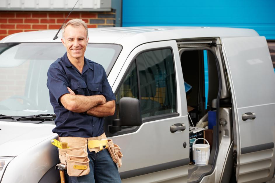 Ein Handwerker steht vor einem Auto