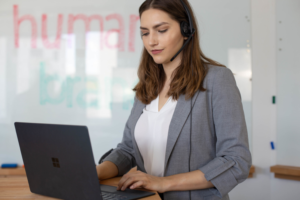 eine junge Frau mit braunen Haaren steht mit ihrem Laptop im Besprechungsraum
