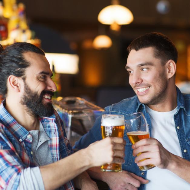 Zwei Männer lächeln sich an und prosten sich zu