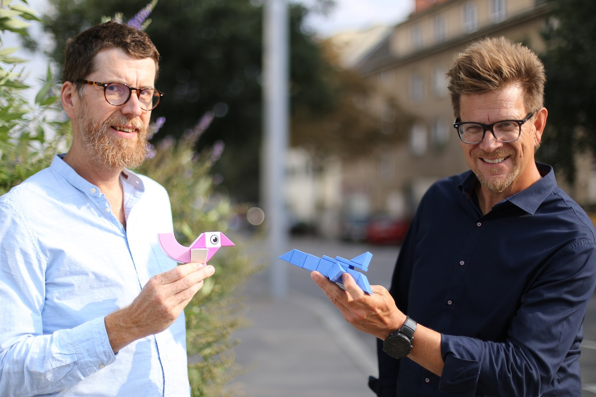 Zwei Männer mit Brille halten Figuren in der Hand