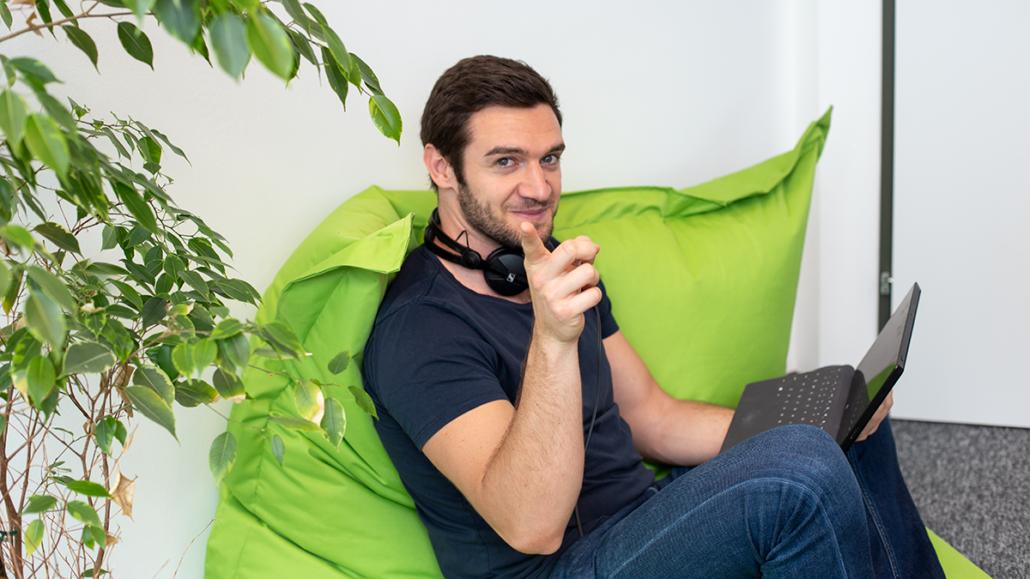 ein junger Mann mit braunen Haaren sitzt auf einem grünen Sitzsack und sieht in die Kamera