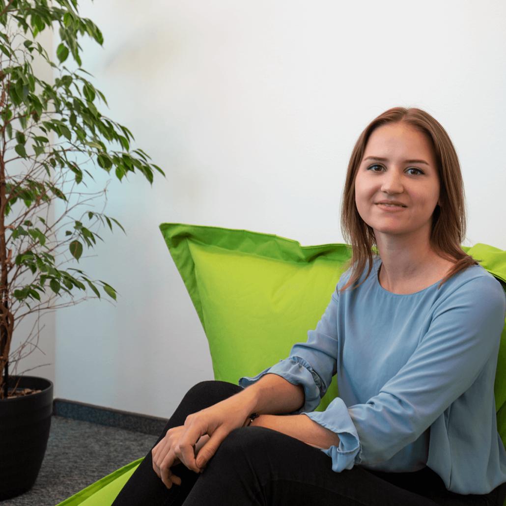 eine junge Frau mit braunen Haaren sitzt auf einem grünen Sitzsack und lächelt in die Kamera