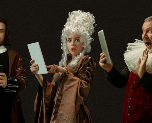 drei Männer und eine Frau mit weißer Perücke in vintage renaissance Kleidung haben Handys und Tablets in den Händen und schauen erschrocken in die Kamera