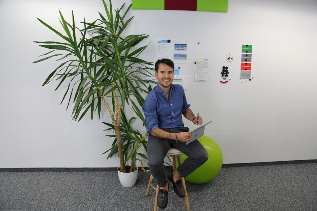 Ein Mann sitzt mit einem Notebook auf einen Stuhl in einem Büro und lächelt in die Kamera