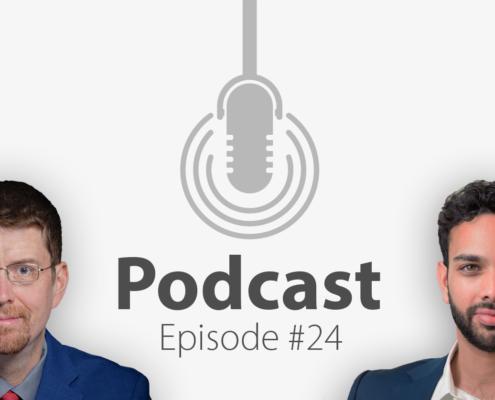Zwei Männer im Anzug lächeln in die Kamera, in der Mitte hängt ein Mikrofon.