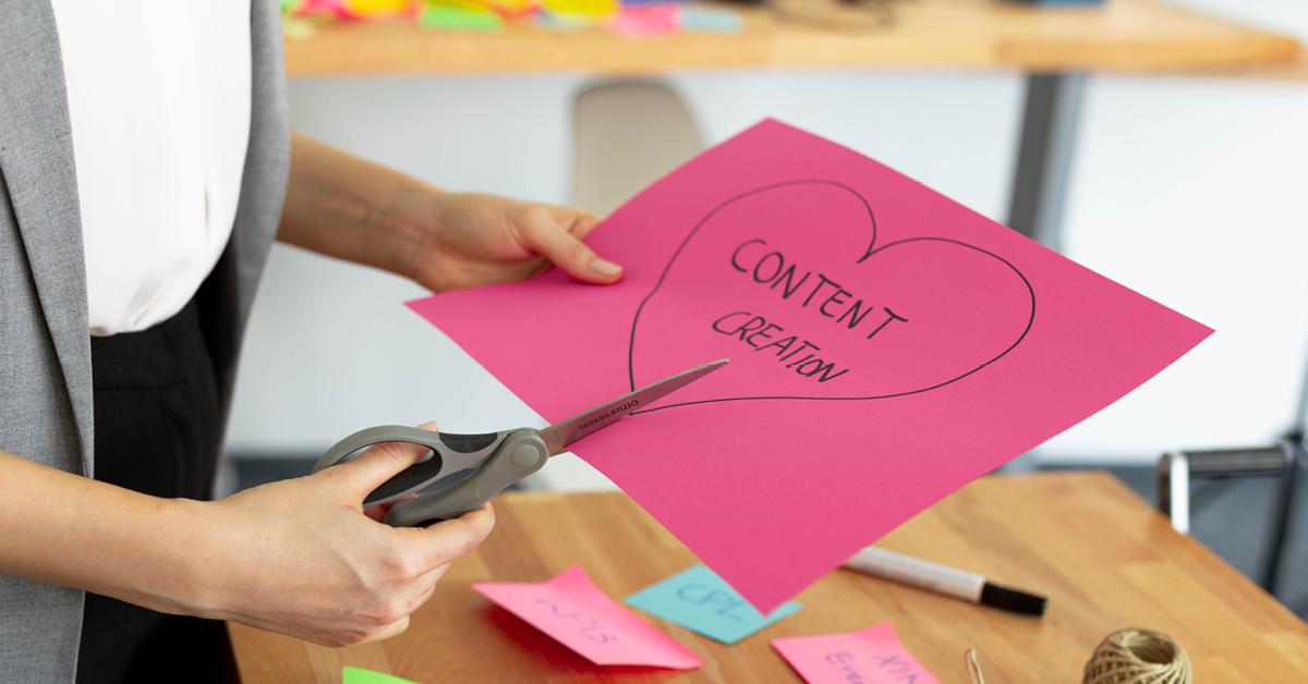 Eine Frau schneidet ein rosa Herz aus, auf dem Content Creation steht